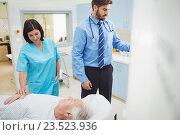 Купить «A patient is loaded into an mri machine while doctor and technician watching», фото № 23523936, снято 9 июля 2016 г. (c) Wavebreak Media / Фотобанк Лори