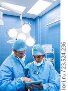 Купить «Surgeons discussing over digital tablet in operation room», фото № 23524236, снято 2 июля 2016 г. (c) Wavebreak Media / Фотобанк Лори
