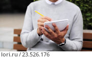 Купить «man with notebook or diary writing on city street», видеоролик № 23526176, снято 26 августа 2016 г. (c) Syda Productions / Фотобанк Лори