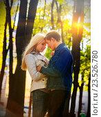 Купить «Young couple hugging and flirting in park.», фото № 23526780, снято 7 октября 2015 г. (c) Gennadiy Poznyakov / Фотобанк Лори