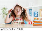 preschooler child girl with book over her head. Стоковое фото, фотограф Оксана Кузьмина / Фотобанк Лори