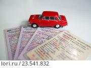 """Красная игрушка машина """"Жигули"""" на фоне свидетельства о регистрации автомобиля. Стоковое фото, фотограф Татьяна Руденко / Фотобанк Лори"""