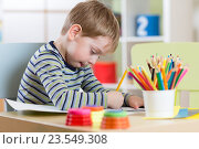 Preschool child use pencils and paints for homework received from kindergarten. Стоковое фото, фотограф Оксана Кузьмина / Фотобанк Лори