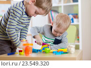 Купить «Kids Play Modeling Plasticine, Children Mold Colorful Clay Dough. Preschooler Playing Together», фото № 23549320, снято 23 февраля 2016 г. (c) Оксана Кузьмина / Фотобанк Лори