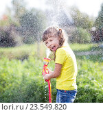 Купить «Cheerful kid watering plants from hose spray in garden at backyard of house sunny summertime», фото № 23549820, снято 3 сентября 2015 г. (c) Оксана Кузьмина / Фотобанк Лори