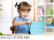Купить «child girl playing with a digital tablet at home», фото № 23558444, снято 24 сентября 2015 г. (c) Оксана Кузьмина / Фотобанк Лори