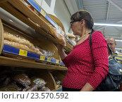 Купить «Пожилая женщина выбирает хлеб в супермаркете», фото № 23570592, снято 10 июня 2016 г. (c) Вячеслав Палес / Фотобанк Лори
