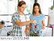 Young people decorating christmas tree in office, фото № 23572848, снято 14 декабря 2014 г. (c) Sergey Nivens / Фотобанк Лори
