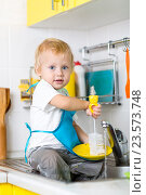 Купить «Child boy washing dishes and having fun in the kitchen», фото № 23573748, снято 13 октября 2015 г. (c) Оксана Кузьмина / Фотобанк Лори