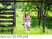 Купить «Молодая женщина катается на качелях летним днём», эксклюзивное фото № 23576224, снято 21 июня 2016 г. (c) Игорь Низов / Фотобанк Лори