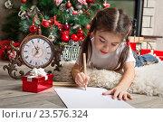 Купить «Маленькая девочка пишет письмо Санта-Клаусу у елки», фото № 23576324, снято 2 ноября 2013 г. (c) Оксана Гильман / Фотобанк Лори