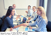 Купить «smiling business people shaking hands in office», фото № 23577452, снято 25 октября 2014 г. (c) Syda Productions / Фотобанк Лори