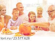 Купить «happy family sitting with pumpkins at home», фото № 23577628, снято 14 сентября 2014 г. (c) Syda Productions / Фотобанк Лори
