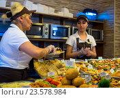 Работники кафе на раздаче готовят выбранные блюда к выдаче (2016 год). Редакционное фото, фотограф Вячеслав Палес / Фотобанк Лори