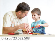Купить «Dad and kid boy working together», фото № 23582508, снято 6 ноября 2014 г. (c) Оксана Кузьмина / Фотобанк Лори
