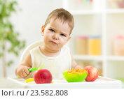 Купить «displeased kid boy with healthy food at kitchen», фото № 23582808, снято 17 октября 2014 г. (c) Оксана Кузьмина / Фотобанк Лори