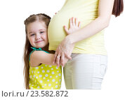 Купить «Cute child girl embracing pregnant mother», фото № 23582872, снято 5 марта 2015 г. (c) Оксана Кузьмина / Фотобанк Лори