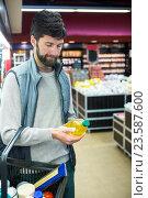 Купить «Man holding oil bottle shopping basket», фото № 23587600, снято 9 мая 2016 г. (c) Wavebreak Media / Фотобанк Лори