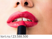Купить «Beautiful woman applying red lipstick on lips against black background», фото № 23588500, снято 15 февраля 2016 г. (c) Wavebreak Media / Фотобанк Лори