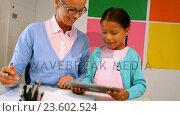 Купить «Schoolgirl and teacher using digital tablet in classroom», видеоролик № 23602524, снято 4 апреля 2020 г. (c) Wavebreak Media / Фотобанк Лори