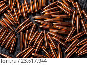 Купить «Placer copper bullets on a dark wooden background», фото № 23617944, снято 21 июля 2018 г. (c) age Fotostock / Фотобанк Лори