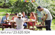 Купить «friends having barbecue party at summer garden», видеоролик № 23620924, снято 7 сентября 2016 г. (c) Syda Productions / Фотобанк Лори