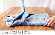 woman folding denim jacket on wooden table at home. Стоковое видео, видеограф Syda Productions / Фотобанк Лори