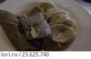 Купить «Dumplings and stuffed grape leaves», видеоролик № 23625740, снято 4 июня 2016 г. (c) Данил Руденко / Фотобанк Лори