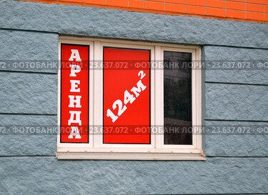 Объявление о сдаче в аренду в окне помещения на первом этаже новостройки