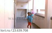 Купить «Cute schoolboy with gift running in corridor», видеоролик № 23639708, снято 11 июля 2020 г. (c) Wavebreak Media / Фотобанк Лори