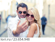 Купить «smiling couple with smartphone in the city», фото № 23654948, снято 14 июля 2013 г. (c) Syda Productions / Фотобанк Лори
