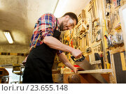Купить «carpenter working with saw and wood at workshop», фото № 23655148, снято 14 мая 2016 г. (c) Syda Productions / Фотобанк Лори