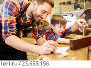Купить «dad and son with ruler measuring plank at workshop», фото № 23655156, снято 14 мая 2016 г. (c) Syda Productions / Фотобанк Лори