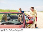 Купить «happy friends pushing broken cabriolet car», фото № 23655624, снято 28 мая 2016 г. (c) Syda Productions / Фотобанк Лори