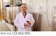 Купить «winemaker in lab coat examining sample of wine», видеоролик № 23662956, снято 7 сентября 2016 г. (c) Яков Филимонов / Фотобанк Лори