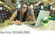 Купить «Девушка с очками работает на компьютере и записывает информацию в блокнот», видеоролик № 23662992, снято 23 сентября 2016 г. (c) Виктор Аллин / Фотобанк Лори