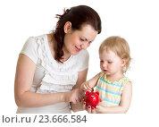 Купить «happy mother and kid put coins into daughter's piggybank», фото № 23666584, снято 7 мая 2014 г. (c) Оксана Кузьмина / Фотобанк Лори
