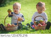 Мальчик и девочка с яблоками в корзинках сидят на лужайке. Стоковое фото, фотограф Вероника Галкина / Фотобанк Лори