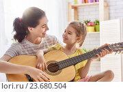 Купить «Mother and daughter playing guitar», фото № 23680504, снято 6 июня 2016 г. (c) Константин Юганов / Фотобанк Лори