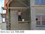 Купить «Рабочий штукатурит фасад коттеджа, стоя на строительных лесах», фото № 23708688, снято 1 июня 2016 г. (c) Ирина Борсученко / Фотобанк Лори