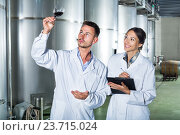 Купить «Man and woman employees on winery manufactory», фото № 23715024, снято 28 мая 2018 г. (c) Яков Филимонов / Фотобанк Лори