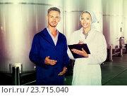 Купить «two workers in coats on winery manufactory», фото № 23715040, снято 28 мая 2018 г. (c) Яков Филимонов / Фотобанк Лори