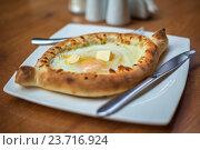 Аджарский хачапури с яйцами на столе. Стоковое фото, фотограф Koba Samurkasov / Фотобанк Лори