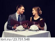 Купить «smiling couple with menus at restaurant», фото № 23731548, снято 9 марта 2014 г. (c) Syda Productions / Фотобанк Лори
