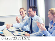 Купить «smiling business team shaking hands in office», фото № 23731572, снято 25 октября 2014 г. (c) Syda Productions / Фотобанк Лори