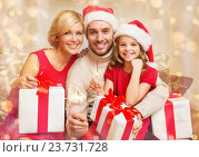 Купить «smiling family holding gift boxes and sparkles», фото № 23731728, снято 26 октября 2013 г. (c) Syda Productions / Фотобанк Лори