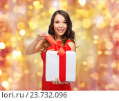 Купить «smiling woman in red dress with christmas gift», фото № 23732096, снято 22 сентября 2013 г. (c) Syda Productions / Фотобанк Лори