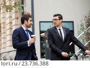 Купить «Two young businessmen with a bike in city centre», фото № 23736388, снято 4 апреля 2015 г. (c) Sergey Nivens / Фотобанк Лори