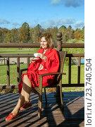 Купить «Женщина в красном пледе сидит в кресле на  веранде с чашкой кофе», фото № 23740504, снято 1 октября 2016 г. (c) Юлия Кузнецова / Фотобанк Лори