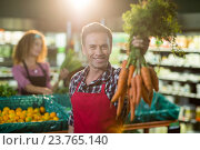 Купить «Smiling male staff holding bunch of carrots in organic section», фото № 23765140, снято 17 мая 2016 г. (c) Wavebreak Media / Фотобанк Лори